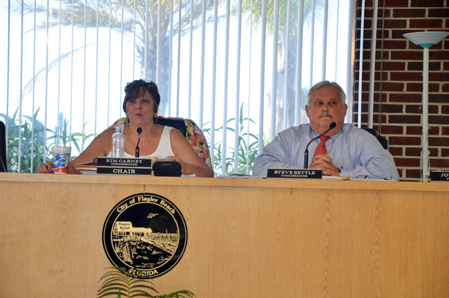 Kim Carney, who chairs the Flagler Beach City Commission, devoted a lengthy presentation to justify her opposition to the city purchase of a $600,00 fire truck, which Commissioner Steve Settle, right, has advocated for. (© FlaglerLive)