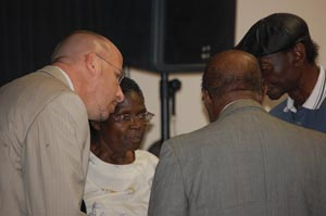 The huddle before the meeting: Carver Gym advocates, from left, Chris Borgmann, Rev. Daisy Henry, Rev. Frank Giddens and Aaron McKinney (FlaglerLive)
