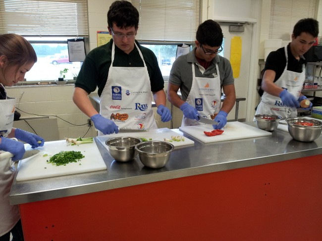 Chefs in the making: Amanda Hale, Dylan Areizaga, Mathew Sousa and Ronnie Stedman preparing food to cater a dinner for the Flagler Palm Coast High School girls weightlifting team. (© FlaglerLive)