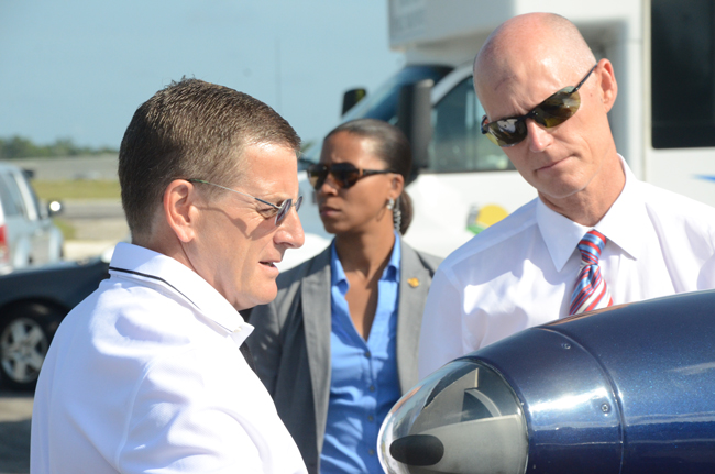 Aveo Engineering's Christian Nielsen, left, shows Gov. Rick Scott one of his company's LED lights before the groundbreaking at the Flagler County Airport in late July. Construction on Aveo's hangar there should start soon. (© FlaglerLive)