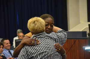 The Flagler County Youth Center's Cheryl Massaro, who is organizing the golf tournament, hugs Marian Irvin, who chairs the Fosuc on Flagler board of directors. They were at an August meeting of the County Commission, where Massaro handed over the Pass It On Award to Irvin. The award recognizes individuals  for their community service. Click on the image for larger view. (© FlaglerLive)