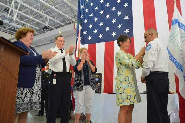 Lisa Forete pins her husband Jerry Forte's Chief badge as he took over the Palm Coast Fire Department's leadership this afternoon, from the retiring Mike Beadle, left, whoi was flanked by his wife Deedee to the right and Deputy City Clerk Kate Settle. (© FlaglerLive)