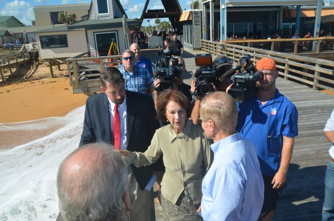 An image from last year's visit by Sen. Bill Nelson, after Hurricane Matthew, that aptly captured the hierarchy of levers, with Craig Coffey, the county administrator, next to then-County Commissioner Barbara Revels, in the foreground, with Nelson, and Steve Garten in the far distance, behind IT Director Jarrod Shupe to the left. (c FlaglerLive)