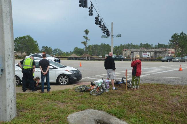 The cyclist's roommate, left, arrived at the scene about half an our after the crash and was greatly distraught, eventually requiring the intervention of paramedics, but she was not taken to a hospital. Her bicycle is in the foreground, the victim's, which was struck, is nearer the road. Click on the image for larger view. (c FlaglerLive)