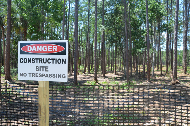 The former homeless camp near the library has been razed of human beings and replaced with a no-trespassing sign even though no construction has yet been approved, or permitted. (© FlaglerLive)
