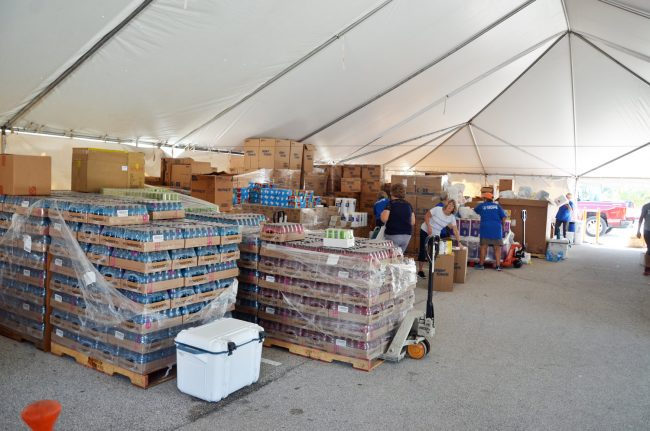 The relief stocks under Convoy of Hope's big tent at Santa Maria del Mar Church's parking lot. Click on the image for larger view. (© FlaglerLive)