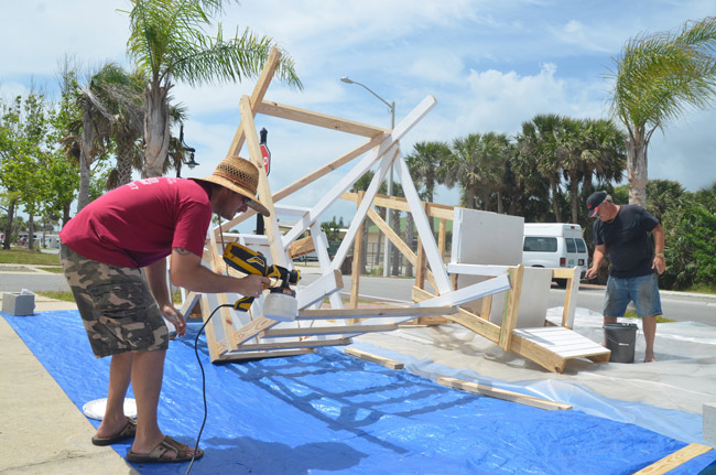 Eric Cooley, left, and Commissioner Rick Belhumeur last Saturday, painting the first two of nine lifeguard towers. Additional volunteers lent a hand during the week to get the towers painted. (© FlaglerLive)