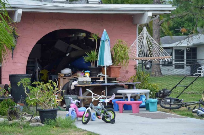 The garage area at 1 Cooper Lane, a mixture of toys and more aged clutter, immediately after authorities left the property Friday afternoon. (c FlaglerLive. Click on the image for larger view.)