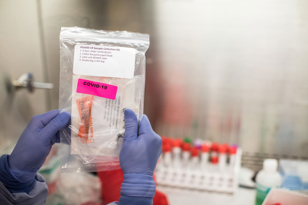 A clinical lab technician at the UW Medicine Virology laboratory in Seattle processes patient samples for COVID-19 on March 11. (Dan DeLong for KHN)