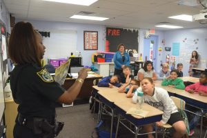 Flagler County Sheriff's corrections deputy Sheria Woods had been on duty 16 hours before coming to the read-in. Her students had no right to seem more tired than she was, particularly since she did not let on. Click on the image for larger view. (© FlaglerLive)