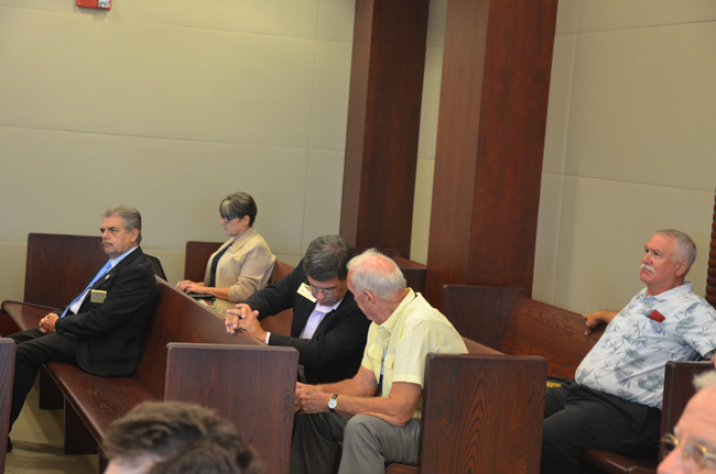 A supermajority of the Flagler County Commission attended a brief hearing before Circuit Judge Dennis Craig this afternoon, where the attorney for an obscure pressure group said he'd file a case alleging that commissioners were illegally 'polled' before a key vote last year. The attorney provided no evidence. The commissioners from left are George Hanns,  Nate McLaughlin, Charlie Ericksen and Frank Meeker. The reporter at her laptop is the News-Journal's Julie Murphy. (© FlaglerLive)