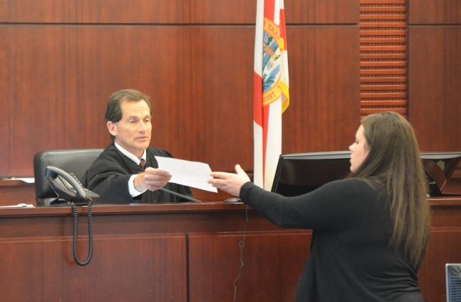 Circuit Judge Dennis Craig hands over the jury verdict form to the clerk to be read. An older woman, a member of C.J. Nelson's family, during a lull in the trial had called out to the judge from the audience, telling him he was doing a great job. The judge smiled and urged the woman to be quiet, as all proceedings are recorded. Click on the image for larger view. She thanked him again when court adjourned. (© FlaglerLive)