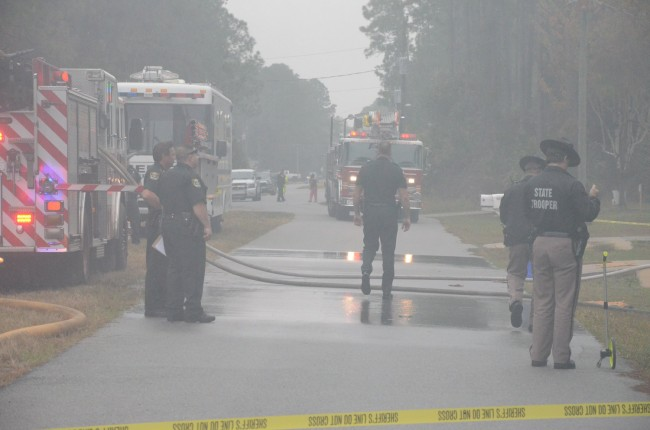 Smoke shrouded authorities at the scene soon after the crash, as firemen battled flames. Click on the image for larger view. (© FlaglerLive)