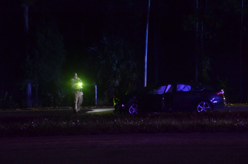A Florida Highway Patrol traffic homicide investigator examines one of the two vehicles involved in tonight's crash. (© FlaglerLive)