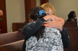 Carol Eure hugs Rebecca Crowley, who'd been the victim of the Sharps Liquor robbery. Eure was with Crowley as both attended every step of the case as it made its way to trial. Click on the image for larger view. (© FlaglerLive)