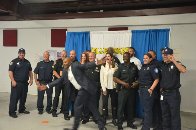 Belle Terre Principal Terence Culver photobombs the dozen-odd first responders, among them Sheriff Rick Staly, and Palm Coast Mayor Milissa Holland and School Board member Colleen Conklin, toward the end of the read-in. Click on the image for larger view. (© FlaglerLive)