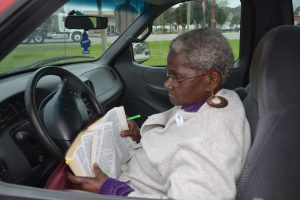 Daisy Henry, a pastor, reading her Bible on Election Day in 2014, when she last served on the Bunnell commission. (© FlaglerLive)