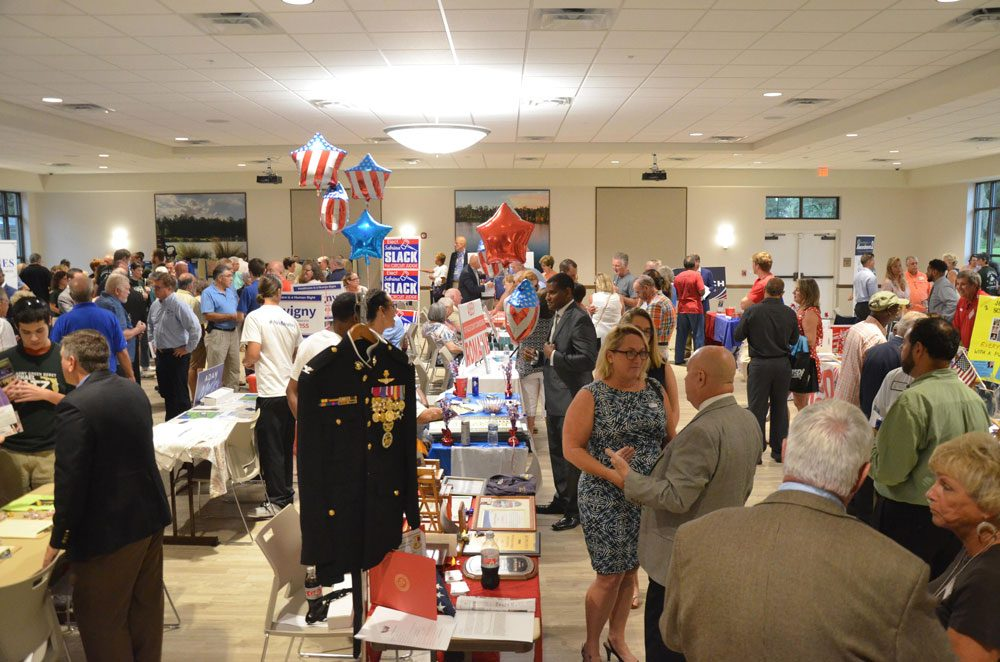 Danielle Anderson, at a campaign event last year (center), heads the Flagler County Republican Club and is a correspondent for the News-Journal. (© FlaglerLive)