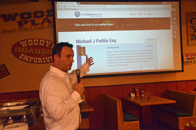 CourtCaseResults.com's Darren McGuire walking guests through the website's functions at its launch party at Woody's BarBQ Monday evening. (© FlaglerLive)