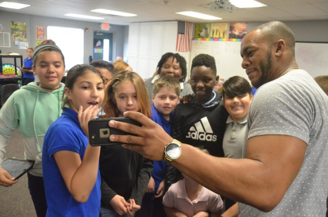 His reading of Ellington over, mixed martial arts competitor Davaughn Brown showed fifth graders images of his latest fight. (© FlaglerLive)
