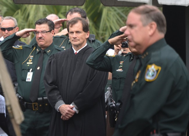 David O'Brien, saluting next to Flagler County Circuit Judge Dennis Craig, during Sheriff Manfre's swearing-in last January. Staly is in the foreground, to the right. Click on the image for larger view. (© FlaglerLive)