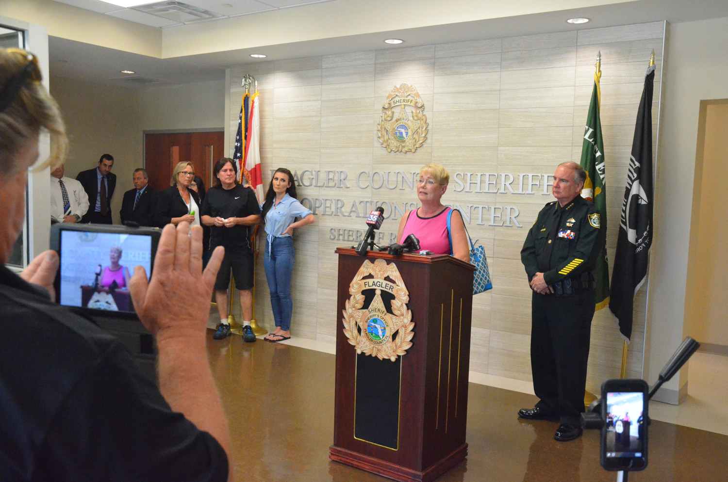Renée Deangelis, mother of Savannah, 23, who died of an overdose last fall, speaks to the press this afternoon, with her husband, Charles, and her daughter Christina, to the left of the image, and Sheriff Rick Staly to the right. Assistant State Prosecutor Jason Lewis and State Attorney R.J. Larizza are toward the left corner. Click on the image for larger view. (© FlaglerLive)