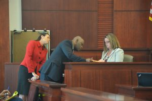 Defense attorney Junior Barrett, center, examining evidence with Jean Blundell, a senior crime lab analyst at the Florida Department of Law Enforcement, with Assistant State Attorney Jennifer Dunton looking on. (c FlaglerLive)