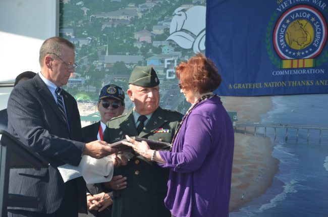 Lt. Col. Harry W. Gilman (ret.), center, accepting the Flagler County Veterans of the Year award from David Lydon and Gary E. Dekay's widow. Click on the image for larger view. (© FlaglerLive)