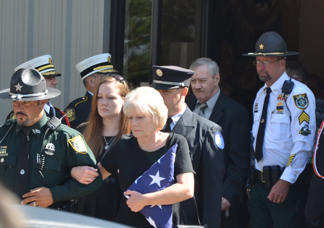 After today's services at Church on the Rock, Joe Delarosby's wife Judy  was led out by Carmine Celico, brother of the late Frank Celico, with her daughter Kelsey behind her, and Joe's father Gerard, who was flanked by Flagler County Sheriff's Sgt. Michael van Buren, a close friend of Joe's and his family. c