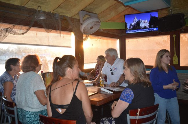 Flagler's Young Democrats, organized by Michelle Atack, right, met at Hidden Treasures in Flagler Beach Thursday evening for a debate watch party. Many more in attendance are sitting out of view. The first group of Democratic presidential candidates debated in Miami Thursday evening. The second group debates tonight. (© FlaglerLive)