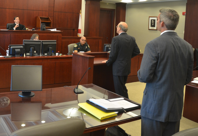 Circuit Judge Dennis Craig heard County Attorney Al Hadeed's argument that the Watchdogs case did not belong in circuit court, and asked Josh Knight, in the foreground, to show him evidence that it does. (© FlaglerLive)