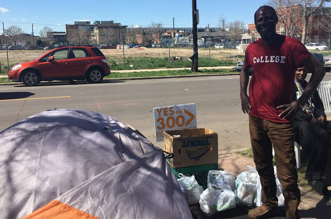 "Jerry Burton, 57, stands beside his tent in downtown Denver. A ballot question before Denver voters next week, an initiative called ""Right to Survive,"" would make sleeping on the streets easier. (Pew Charitable Trust)"