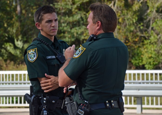Deputy James Gore, left, speaking with Cmdr. Mark Carman at the scene. Click on the image for larger view. (© FlaglerLive)