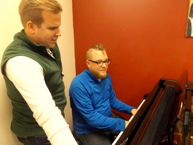 "Director Tyler Adcock, left, and music director Ben Beck peruse the score of ""Songs for a New World."" The 1995 ""song cycle"" will be staged Friday Jan. 12 through Jan. 28 at City Repertory Theatre in Palm Coast. (© FlaglerLive)"