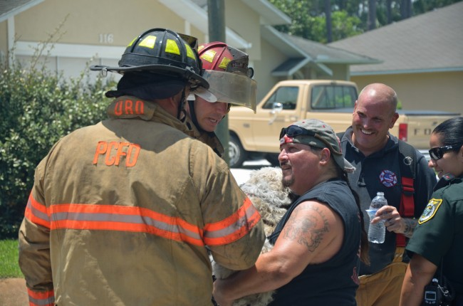 Lt. Jason Wagner and Firefighter Michael Chandley are thanked by the owner of the dog they rescued. Click on the image for larger view. (© FlaglerLive)