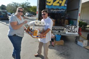 Shannon McCurdy of Palm Coast hands off a batch of donations to Flagler Broadcasting's Kirk Keller this morning at Winn-Dixie. (c FlaglerLive)