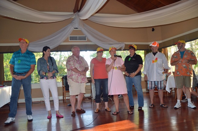 The Duck Dive's headliners. From left, Palm Coast Fire Chief Mike Beadle, former Commissioner Milissa Holland, Mayor Jon Netts, Flagler Chamber President Rebecca DeLorenzo, Tourist Development Director Georgia Turner, Flagler Beach Commissioner Kim Carney, Assistant Superintendent Jacob Oliva, and Auditorium Board Chairman Richard Hamilton. Click on the image for larger view. (© FlaglerLive)