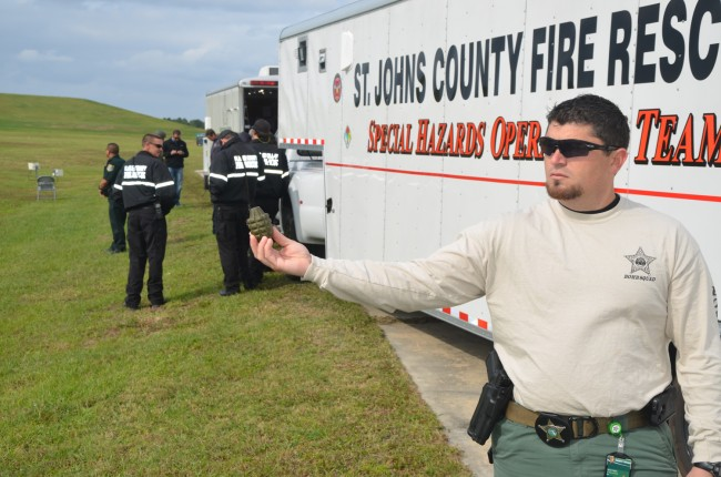 A member of the St. Johns County Sheriiff's Office's bomb squad shows the dud pineapple grenade found at the Flagler County landfill this morning. Click on the image for larger view. (© FlaglerLive)