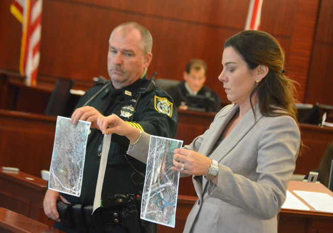 Assistant State Attorney Jennifer Dunton, with help from bailiff John Freshcorn, showed the jury pictures of the wooded area that had looked odd to a detective, and that proved to be the makeshift grave Dorothy Parker dug for her husband, Charles Singer, after killing him in February 2017 in west Flagler. (© FlaglerLive)