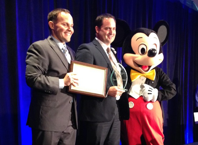 Deputy Chancellor for Educator Quality Brian Dassler, left, gave Dustin Sims the Florida Assistant Principal of the Year  award at the Coronado Springs Resort this afternoon, with Mickey Mouse, an honorary  IB graduate, looking on.