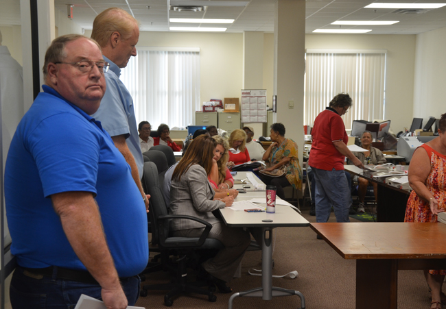 Today's Canvassing Board meeting focused on testing voting machines. Dwayne Weeks (left), husband of Supervisor of Elections Kimberle Weeks, stood by as County Judge Melissa Moore Stens and other members of the board tabulated testing results. (c FlaglerLive)