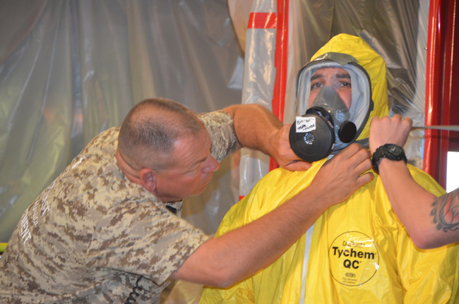 The Palm Coast Fire Department's Lt. Jason Laughren helps firefighter Joey Taci suit up during a demonstration of biohazard response at Palm Coast's Station 25 today. (© FlaglerLive)