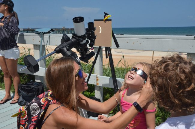 Kailani Raby, 3, of Flagler Beach, with her mother Tiffany Wiggen, catching the eclipse at its peak as it is also refracted by the telescope Scott Spradley had set up on the Flagler Beach Boardwalk this afternoon. Click on the image for larger view. (© FlaglerLive)