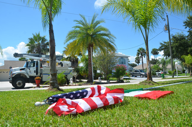 The electrocution victims were attempting to plant the flagpole down the white pipe, alongside the palm tree in the center of the picture, which is itself right below a 13,000-volt power line. (© FlaglerLive)