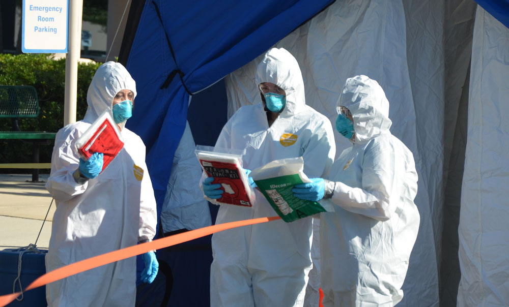 Six years ago local first responders and hospital personnel conducted the largest drill to date to practice for a mass casualty event involving contamination (above). Today, responders and hospital personnel are required to wear personal protective equipment, commonly known as PPE, in many encounters with patients or potential patients as the coronavirus pandemic spreads. (© FlaglerLive)