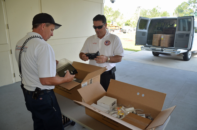They don't come cheap: Flagler County Fire Rescue Capt. Jamie Burnsed, left, and Fire Chief Don petito took delivery of dozens of new radios last year, paid for through a grant. The radios hook into the county's 800 MHz communications system, which is approaching its end, though the radios themselves can be adapted to a new system. (© FlaglerLive)