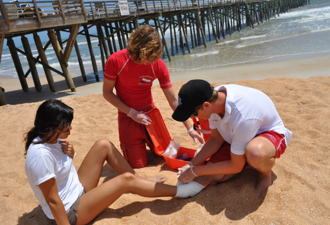 Flagler Beach Lifeguard David Petkovsek wraps a beachgoer's ankle as Andreas Stocker assists. Florida Hospital Flagler recently donated an array of medical supplies to the City of Flagler Beach's Ocean Rescue Services.