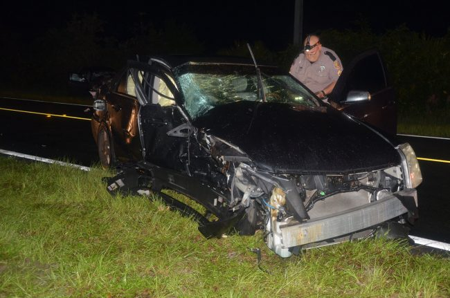 Florida Highway Patrol Traffic Homicide investigator Pete Young examining the Cadillac, which took the brunt of the collision on its passenger side. Click on the image for larger view. (© FlaglerLive)