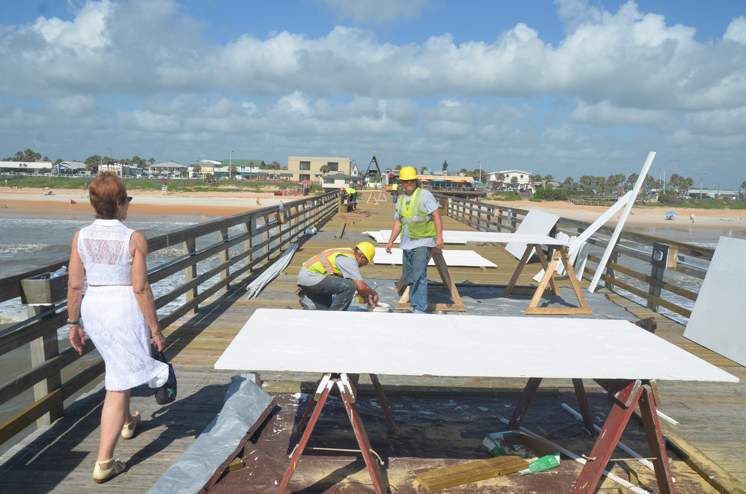 Flagler Beach City Commission Chair Jane Mealy walked to the edge of the the pier for the first time since Hurricane Matthew as workers put on the finishing touches. Standing in the middle was David Marine, one of the workers with the contractor, who happens to live a block and a half away from the pier. Click on the image for larger view. (© FlaglerLive)