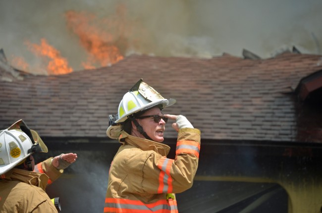 Palm Coast Fire Chief Mike Beadle, in command at the scene, gave the ladder truck crew visual directions from the front yard of the house. It is tradition among fire crews that when a fireman appears in a media picture, he is responsible for buying his squad ice cream. When it's the chief, the highest-quality ice cream is required. Click on the image for larger view. (© FlaglerLive)